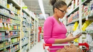 woman reads label of product at grocery store